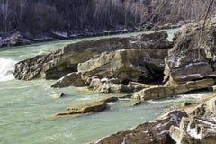 Grande étagère de roche tombée dans une rivière débordante forte, vert bleu Photos libres de droits