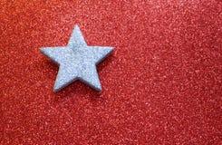 Grande étoile argentée sur le fond rouge rougeoyant lumineux photos stock