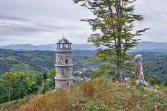 Grande allerta della pietra e dell'albero sopra la collina di Bucina con le montagne di Ohre River Valley e del minerale metallif Fotografia Stock