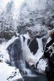 Grande alta cascata nella foresta di inverno della montagna con gli alberi e le precipitazioni nevose innevati Fotografia Stock Libera da Diritti