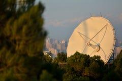 Grande antenne parabolique blanche derrière des arbres avec vue sur Bakou, capitale de l'Azerbaïdjan, à l'arrière-plan Image stock