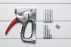 Grande arme à feu d'agrafeuse de tacker avec des agrafes sur le plancher en bois Image stock