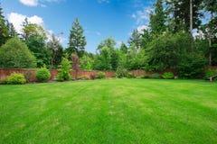 Grande arrière-cour clôturée verte avec des arbres.