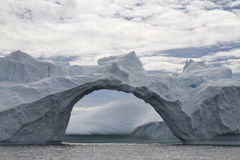 Grande attraverso-arco in un iceberg su un nuvoloso Immagini Stock Libere da Diritti