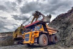 Grande autocarro con cassone ribaltabile della cava Caricando la roccia nello scaricatore caricamento Fotografia Stock