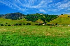 Grande azienda agricola al piede delle colline verdi fotografia stock