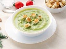 grande bacia branca com sopa de creme verde vegetal dos brócolis, abobrinha, ervilhas verdes no fundo branco, vista lateral imagens de stock royalty free