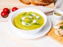 grande bacia branca com sopa de creme verde vegetal dos brócolis, abobrinha, ervilhas verdes no fundo branco, vista lateral imagens de stock