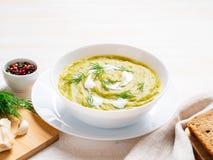 grande bacia branca com sopa de creme verde vegetal dos brócolis, abobrinha, ervilhas verdes no fundo branco, vista lateral imagem de stock royalty free
