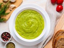 grande bacia branca com sopa de creme verde vegetal dos brócolis, abobrinha, ervilhas verdes no fundo branco, vista superior imagem de stock royalty free