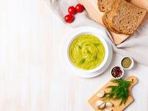 Grande bacia branca com sopa de creme verde vegetal dos brócolis, abobrinha, ervilhas verdes no fundo branco, vista superior, esp fotos de stock