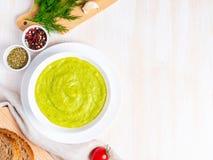 Grande bacia branca com sopa de creme verde vegetal dos brócolis, abobrinha, ervilhas verdes no fundo branco, vista superior, esp foto de stock royalty free