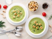 Grande bacia dois branca com sopa de creme verde vegetal dos brócolis, abobrinha, ervilhas verdes no fundo branco, vista superior foto de stock royalty free