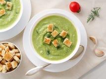 Grande bacia dois branca com sopa de creme verde vegetal dos brócolis, abobrinha, ervilhas verdes no fundo branco, vista superior fotos de stock royalty free
