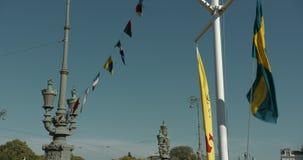 Grande bandiera dello svedese ed altre bandiere su una linea, ondeggiante morbidamente in canale di Gothenburg stock footage