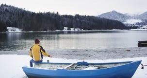 Grande barca blu accanto di un uomo del lago della riva con un rivestimento arancio divertirsi ammirare interamente la vista di u archivi video