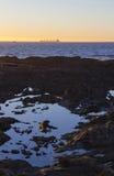 Grande barca fuori in mare al tramonto con lo stagno della roccia Immagine Stock Libera da Diritti