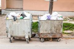 Grande bidone della spazzatura del bidone della spazzatura di due metalli in pieno della lettiera di straripamento che inquina la Fotografie Stock