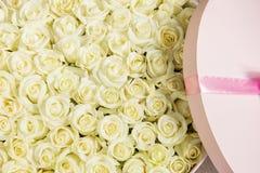 Grande boîte ronde avec les roses blanches enveloppées dans les roses Photographie stock libre de droits