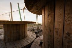 Grande bobina de madeira vazia - carretel de madeira - bobinas de madeira em uma jarda da construção contra um por do sol brilhan imagem de stock