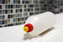 Grande bouteille en plastique avec la colle sur le fond de mosaïque de mur photographie stock