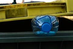 Grande bouteille en plastique bleue dans une poubelle verte jaune - réutilisez pour la nature images libres de droits