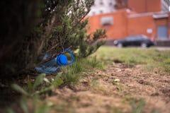 Grande bouteille en plastique bleue se trouvant au sol dans l'arbre dans une for?t de parc - jet?e pas a r?utilis? - d?chets et p photos libres de droits