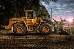 Grande bulldozer al cantiere, al cielo nuvoloso ed al tramonto Immagini Stock