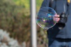 Grande bulle de savon avec l'appareil-photo de transport de l'homme à l'arrière-plan Photo libre de droits