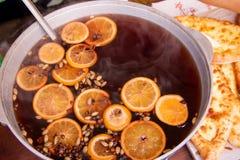 Grande caçarola com as laranjas desbastadas e as especiarias do vinho ferventado com especiarias fotografia de stock royalty free