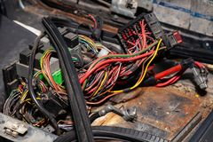 Grande cabo largo com fios coloridos e os conectores e terminais na oficina de reparações prendendo e os eletricistas vermelhos e imagens de stock