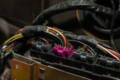 Grande cabo largo com fios coloridos e os conectores e terminais na oficina de repara??es prendendo e os eletricistas vermelhos e imagem de stock royalty free