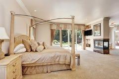 Grande camera da letto cremosa matrice di toni nella casa di lusso Fotografie Stock Libere da Diritti