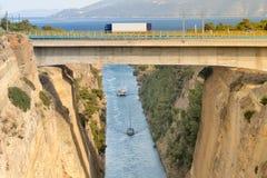Grande camion che attraversa il ponte dell'istmo di Corinto in Grecia mentre le barche stanno viaggiando nel fondo Immagini Stock
