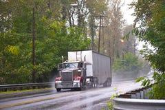 Grande camion classico dell'impianto di perforazione nella pioggia della strada bagnata del tempo Immagini Stock