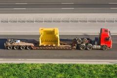 Grande camion con un rimorchio basso della piattaforma che porta a con le grandi parti per le macchine industriali Fotografie Stock