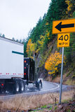 Grande camion nero dei semi dell'impianto di perforazione sulla strada di autunno nella pioggia del tempo Fotografia Stock