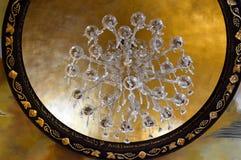 Grande candelabro luxuoso bonito do cristal com pendentes e ornamento e um quadro de ornamento do ouro no cei de pedra alto Fotografia de Stock Royalty Free