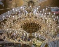 Grande candeliere dorato che pende da un soffitto fotografia stock