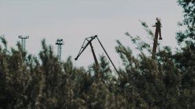 A grande carga do metal cranes sobre atrás de agitar arbustos vídeos de arquivo