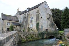 Grande casa com o moinho de água na vila rural inglesa fotos de stock