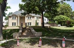 Grande casa de gama alta do tijolo na vizinhança frondosa com foguete 4o de ornamento de julho na parte dianteira Foto de Stock Royalty Free