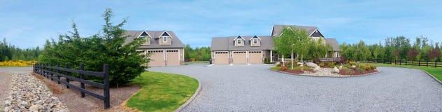 Grande casa di campagna dell'azienda agricola con la strada privata della ghiaia ed il paesaggio verde. Fotografie Stock
