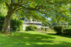 Grande casa marrom exterior com o jardim verde do verão. fotografia de stock