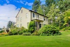 Grande casa marrom exterior com jardim do verão. foto de stock royalty free