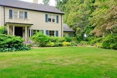 Grande casa marrom exterior com jardim do verão. fotografia de stock royalty free