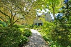 Grande casa marrom exterior com o jardim verde do verão. fotos de stock royalty free