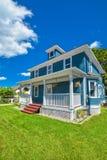 Grande casa residenziale con i punti della porta e patio nella parte anteriore sul fondo del cielo blu immagine stock libera da diritti
