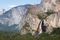 Grande cascade avec un arc-en-ciel de brume en montagnes Photographie stock