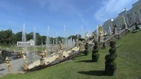 A grande cascata famosa no parque de Peterhof, mostra a fonte de conexão em cascata central, muitas esculturas do ouro vídeos de arquivo